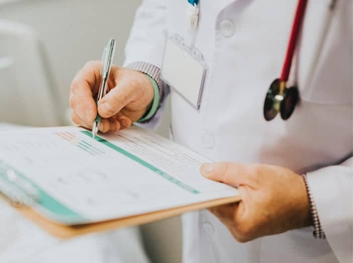 A doctor taking notes on a clipboard